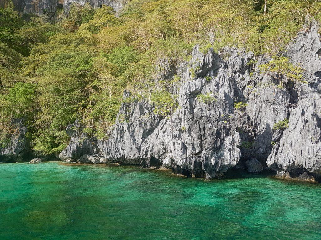 Türkisblaues Meer und schroffe Steine als typische Landschaft des Inselarchipels um El Nido