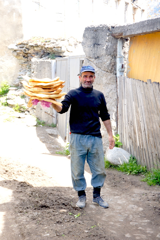 Georgischer Mann mit Stapel an frischem Brot