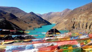 Türkisblauer Stausee mit tibetischen Gebetsfahnen